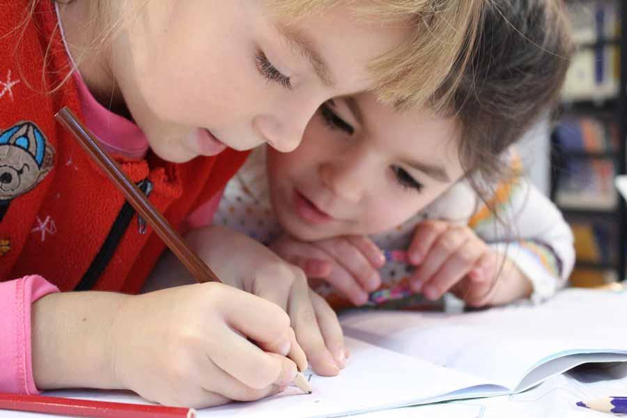 Soutien scolaire, deux enfants écrivent sur un cahier